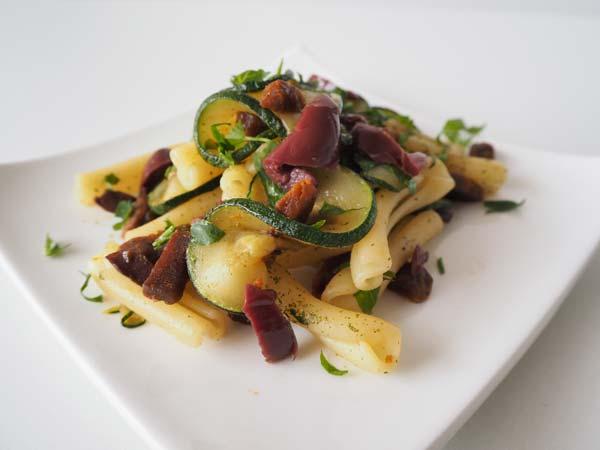Pasta con salami vegano picante, calabacín y olivas