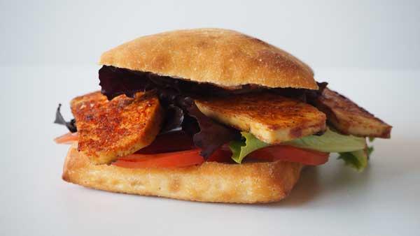 Sandwich vegano de tofu, lechuga, tomate y hummus
