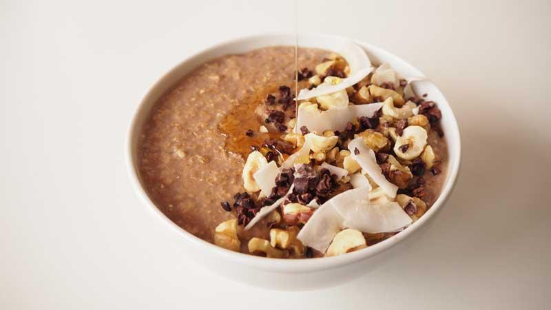 Gachas de avena con leche, chocolate, nueces, avellanas, nibs de cacao, coco y sirope de agave